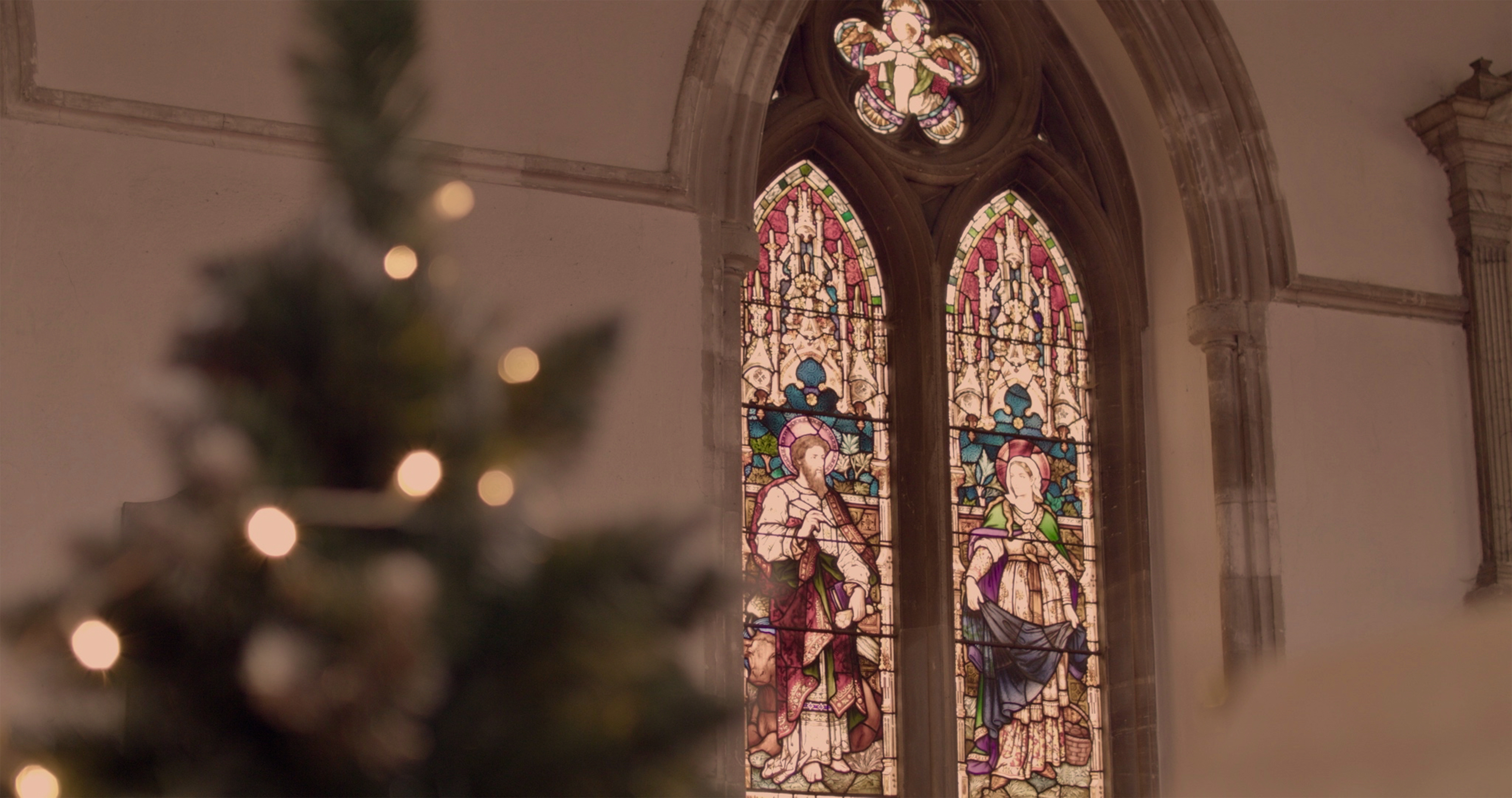 Stained Glass window with a Christmas tree in the foreground
