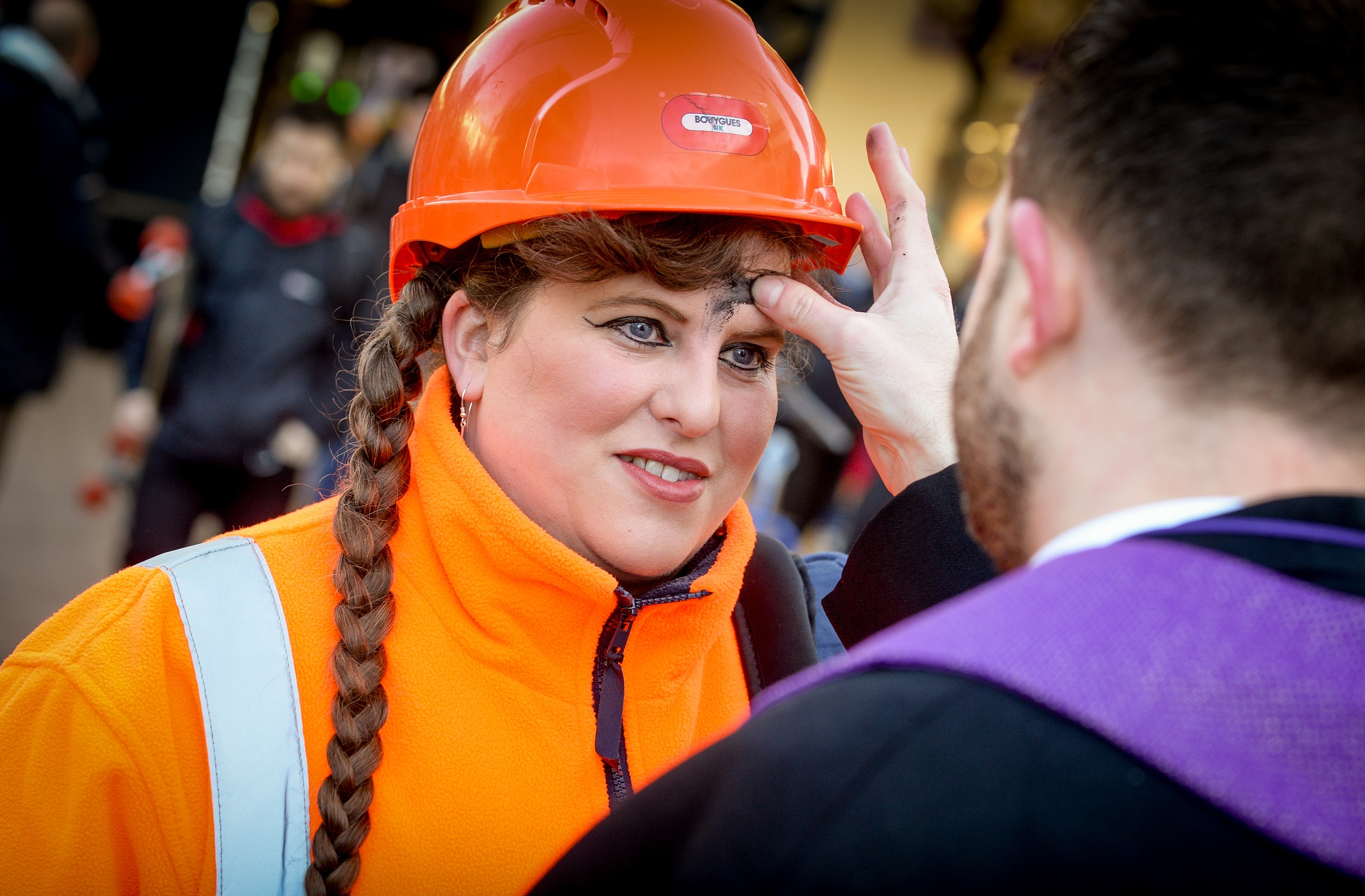 Lady in hard hat being given ash cross on forehead
