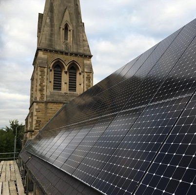 Close up of solar panels on the roof of a church with the spire in the background
