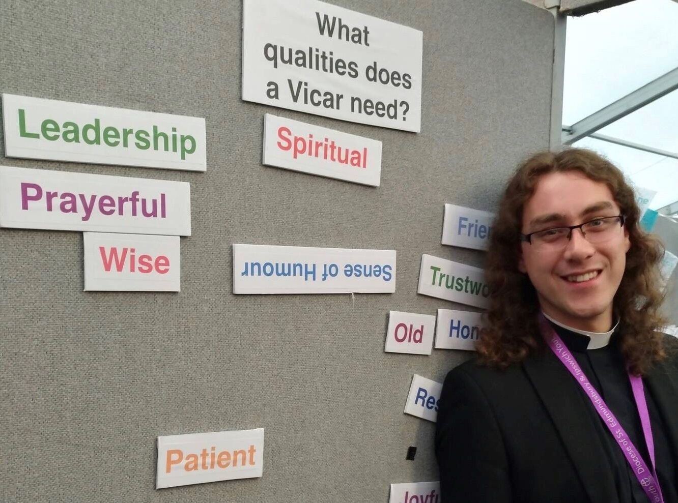 Young vicar standing by a display of qualities needed: Leadership, Spiritual, Prayerful, Wise, Patient, Sense of humour
