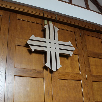 A stylised cross on wood panelling in St Michael's church, Martlesham Heath