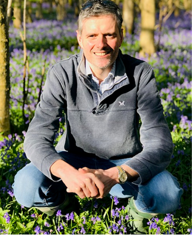 Man crouching in bluebells