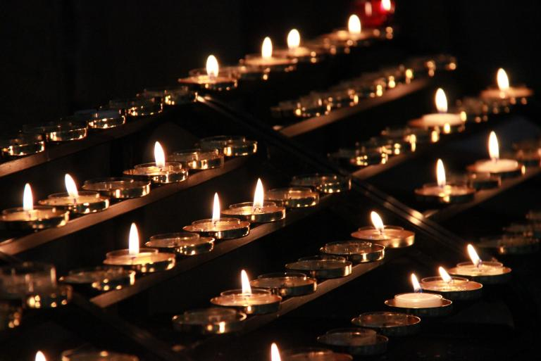 Rows of tealight candles, half lit