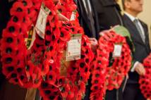People in a row holding wreaths made from poppies