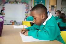 Young school child writing at table in class