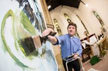 Male clergy member painting canvas inside church