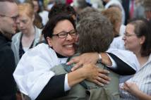 Female clergy member hugging friend and smiling