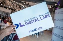 A card with the Digital Labs logo on held up in front of a room of delegates.