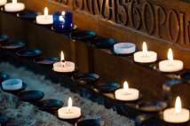 Focus on several white and blue tea-lights burning on a stand in church