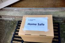 A Home safe parcel sitting outside the front door of someone's house.