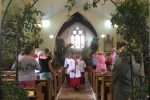 A service is conducted with trees in a church