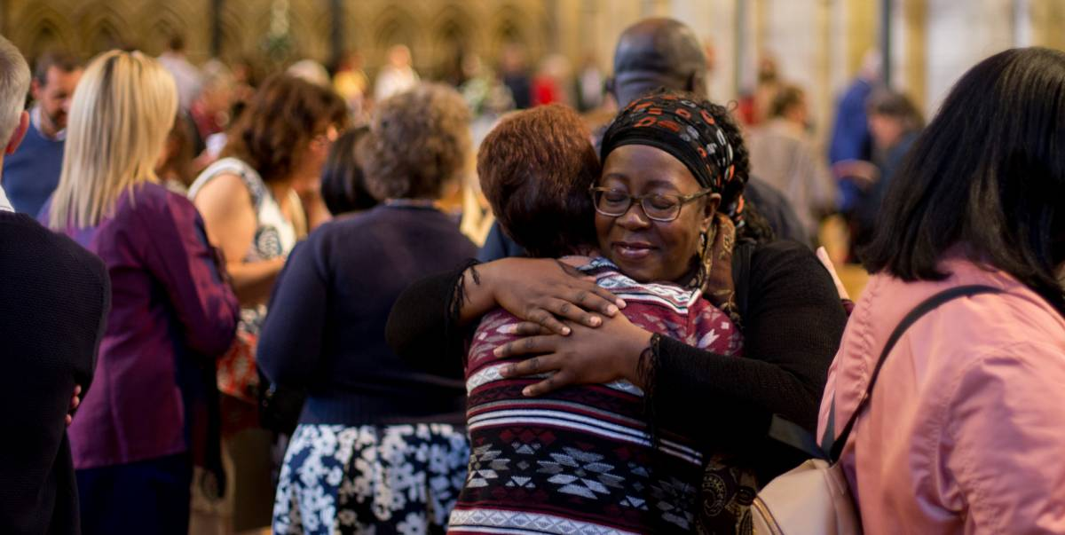 Two women hug inside cathedral