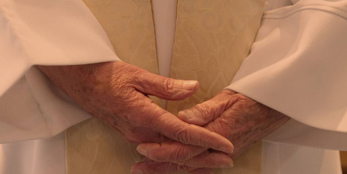 Close up of person wearing robes, hands held held together