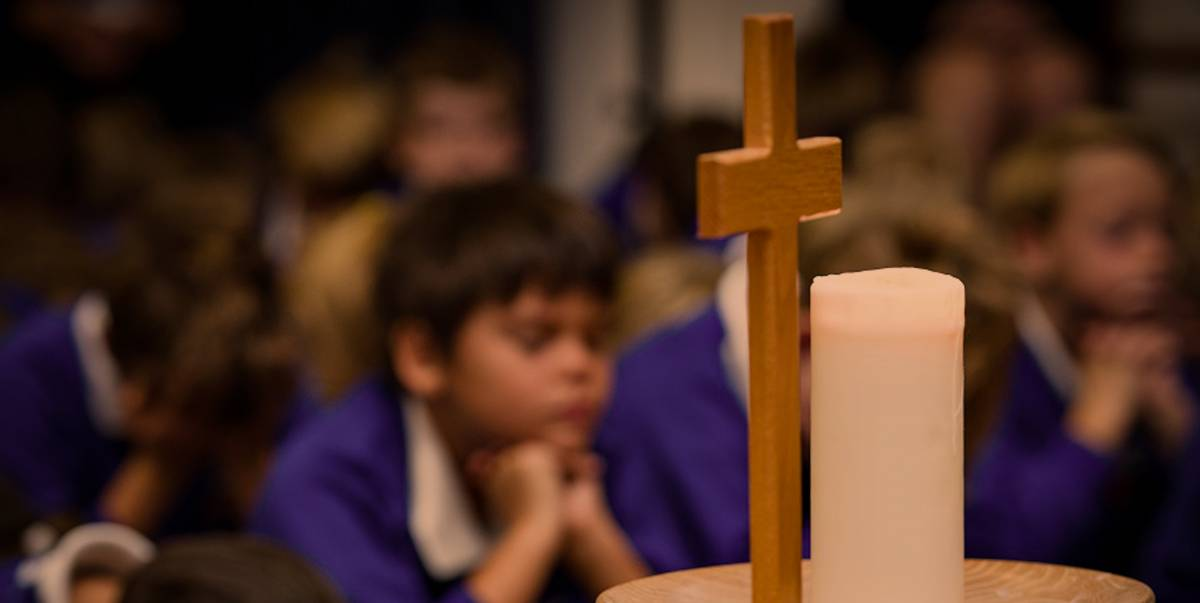 School children praying with cross and candle