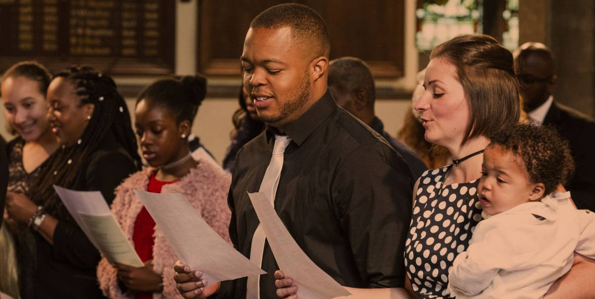 Couple and baby singing in church service