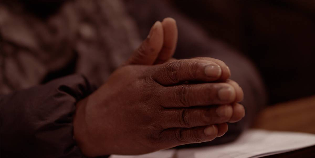 Hands clasped in prayer at a pew in a church.