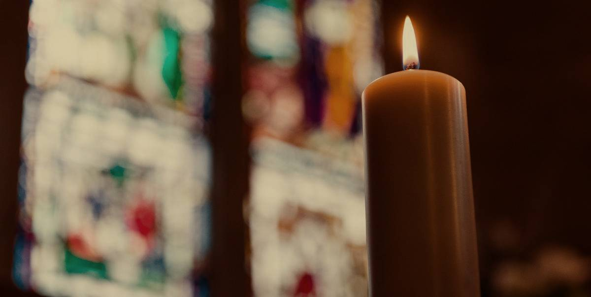 A burning candle in front of a blurry stained glass window.