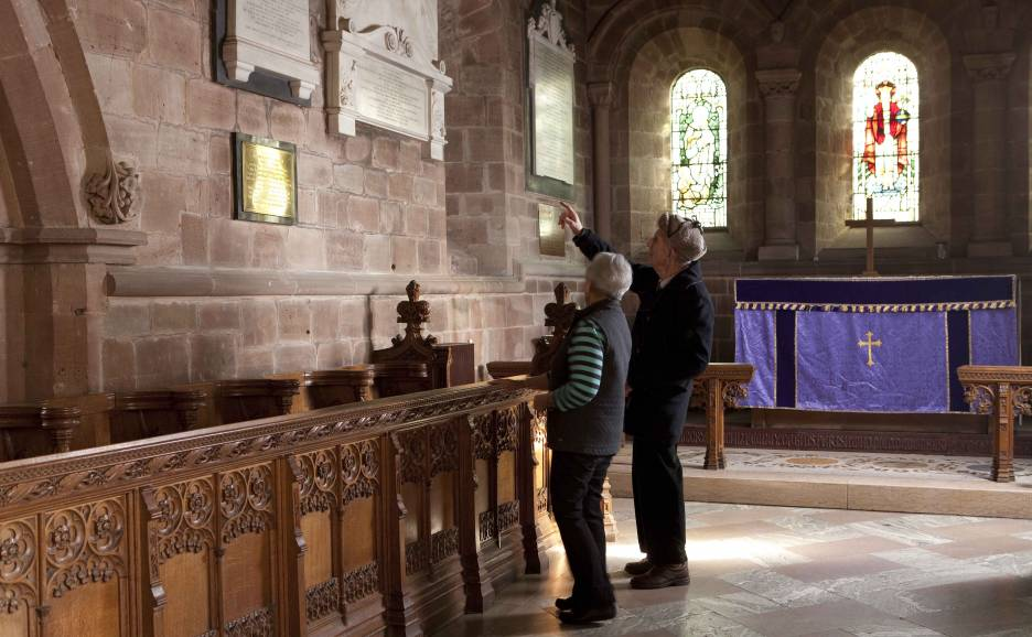 Couple looking at wall memorial inside church