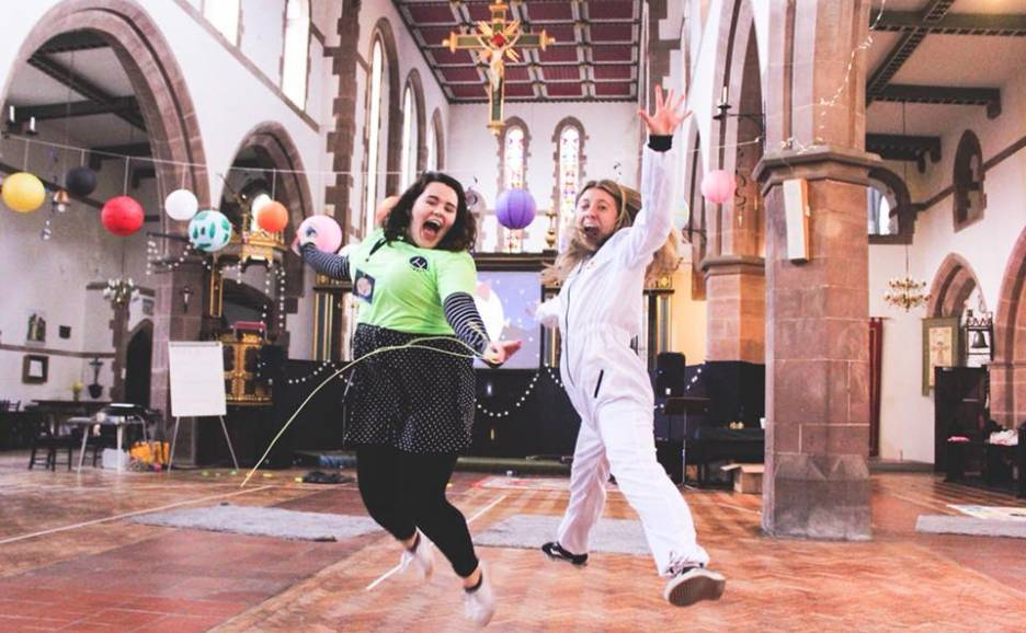 Two girls dressed up jumping in a church with balloons.