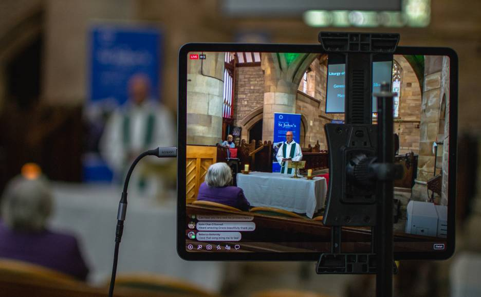 Tablet showing the live stream of a priest leading a church service