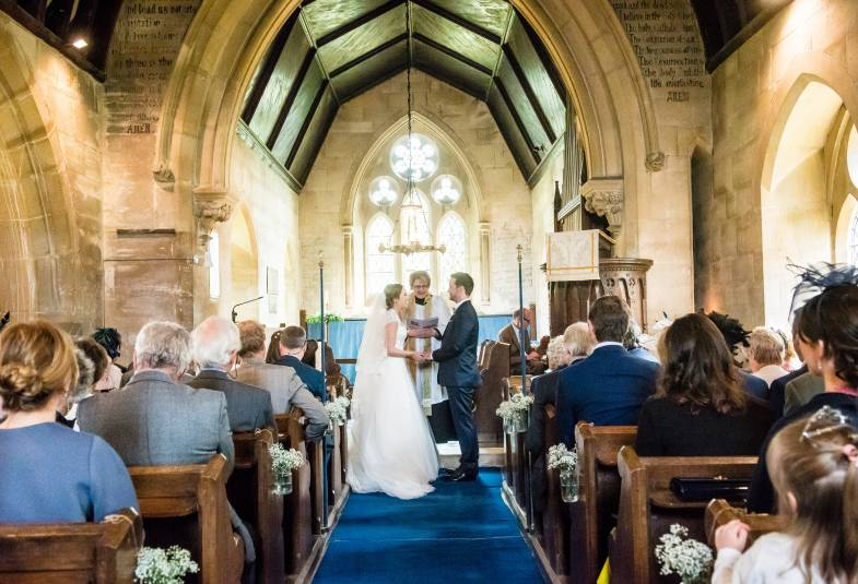 wedding couple at front of church, people in pews