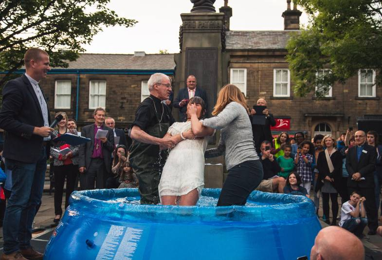 Two people dipping lady into baptismal pool outside