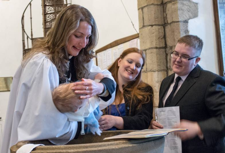 female vicar baptising baby in font, parents standing beside it smiling