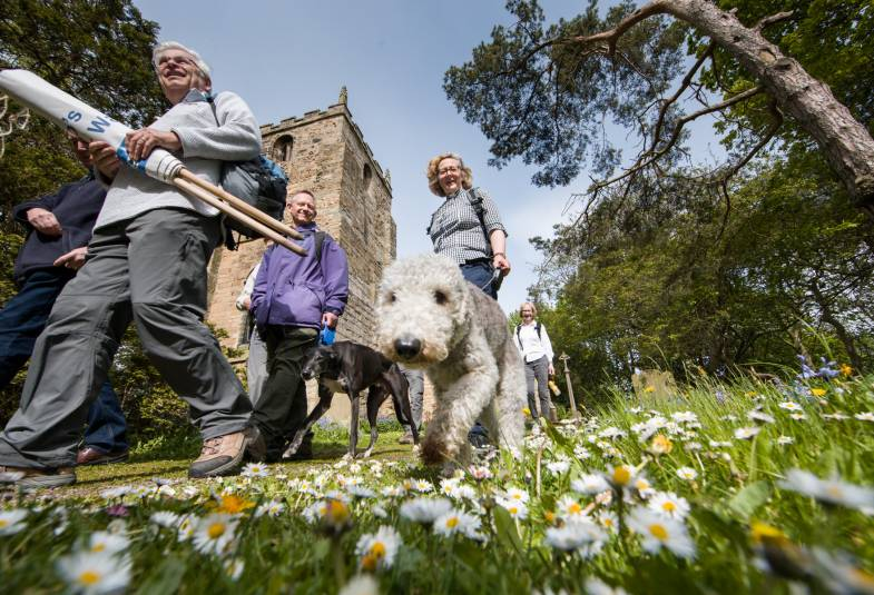 Vicar and parishioners with dogs walk past church on prayer walk