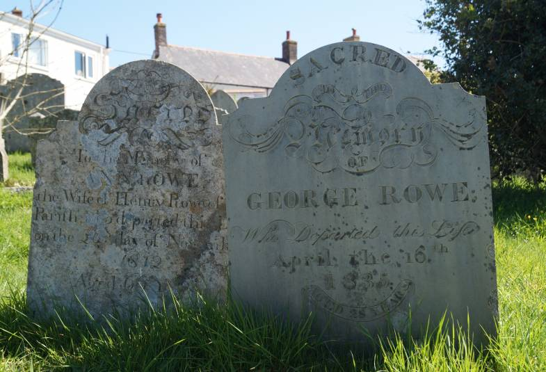 Two old graves in graveyard with tall grass