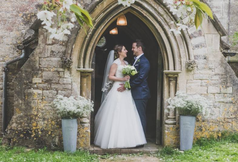 Bride and groom standing in church doorway facing each other