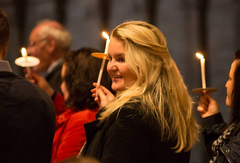 Young woman smiling, holds candle at service