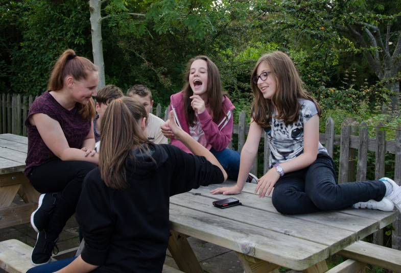 group of teenagers sitting on picnic bench, laughing
