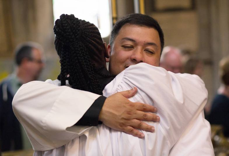 Two new members of clergy hugging