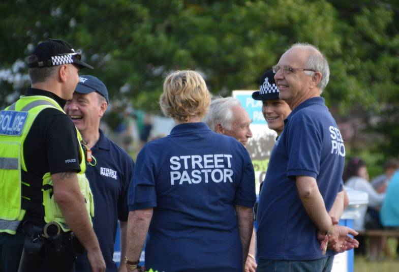 Street pastors and police talking to each other outside