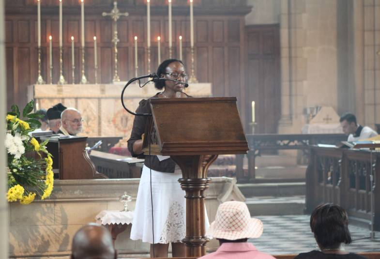 young woman standing at front of church, speaking at wooden lectern