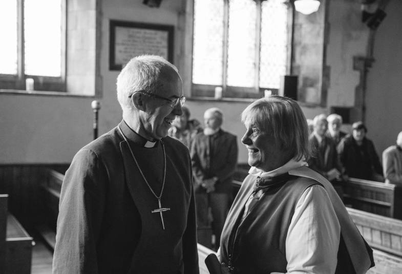 Archbishop of Canterbury laughing with lady in church