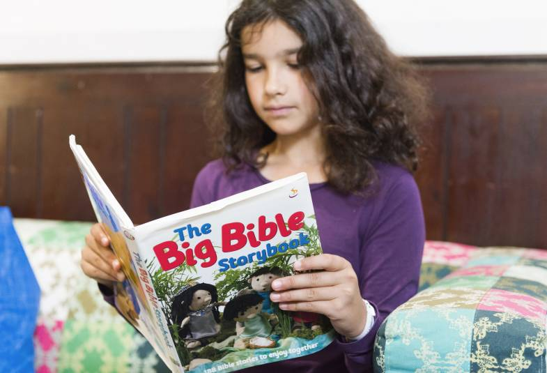 Young girl ready bible storybook