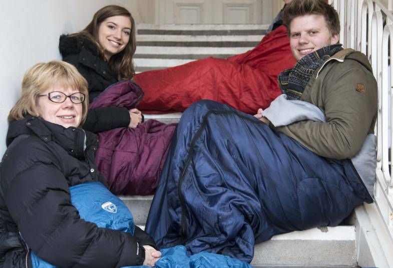 Bishop Sarah Mullally in sleeping bag on stairs with others