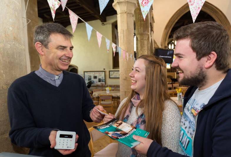Vicar showing contactless payment to couple in church