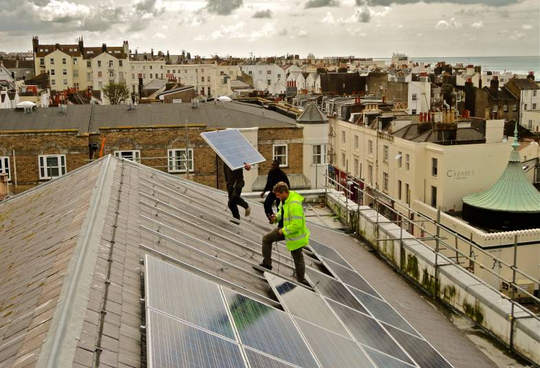 Two men installing solar panels on a church roof with a view of Brighton in the background