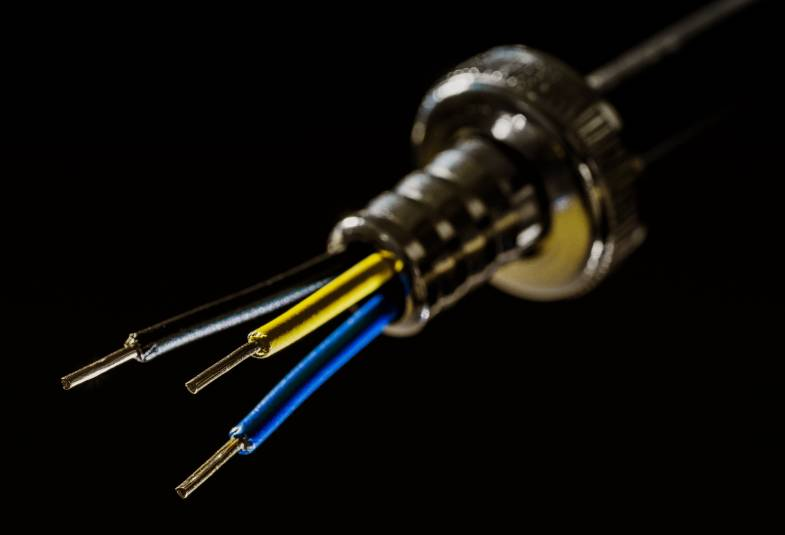 Close up of the ends of a black, yellow and blue electrical wire on black background