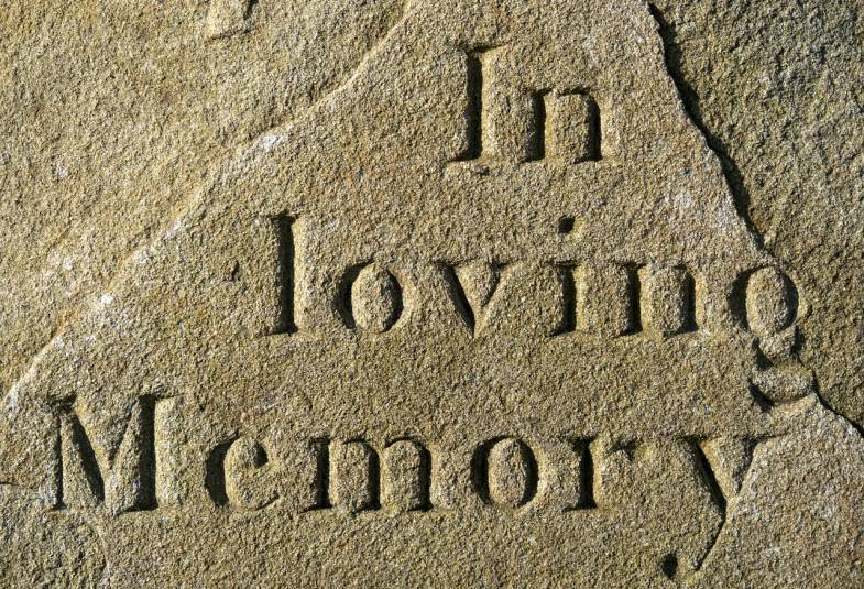 "Close up on carved writing on an old gravestone which says ""In loving memory"""