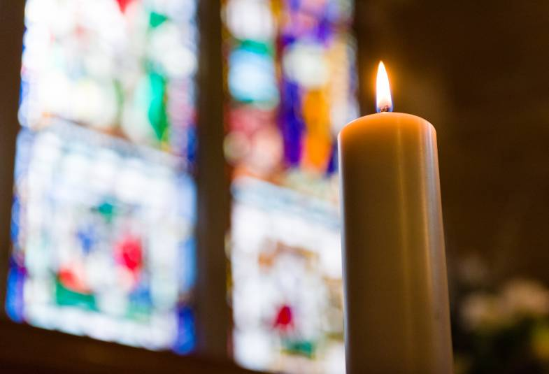 Lit candle in front of stained glass window