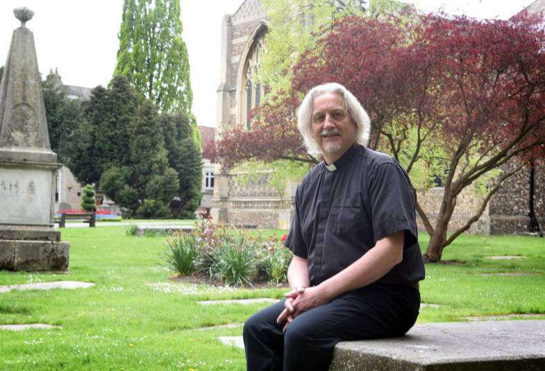 Portrait of Chelmsford Cathedral Dean sitting in churchyard
