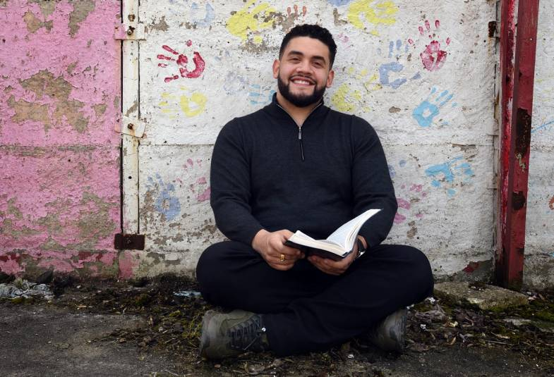 Young man sat smiling with bible