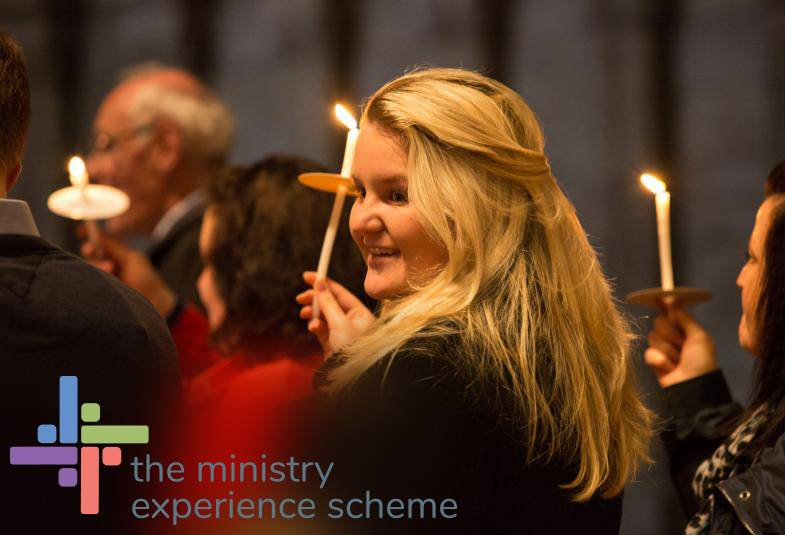 A women holding a candle at a church service smiling. The Ministry Experience Scheme logo is displayed in the bottom left-hand corner.