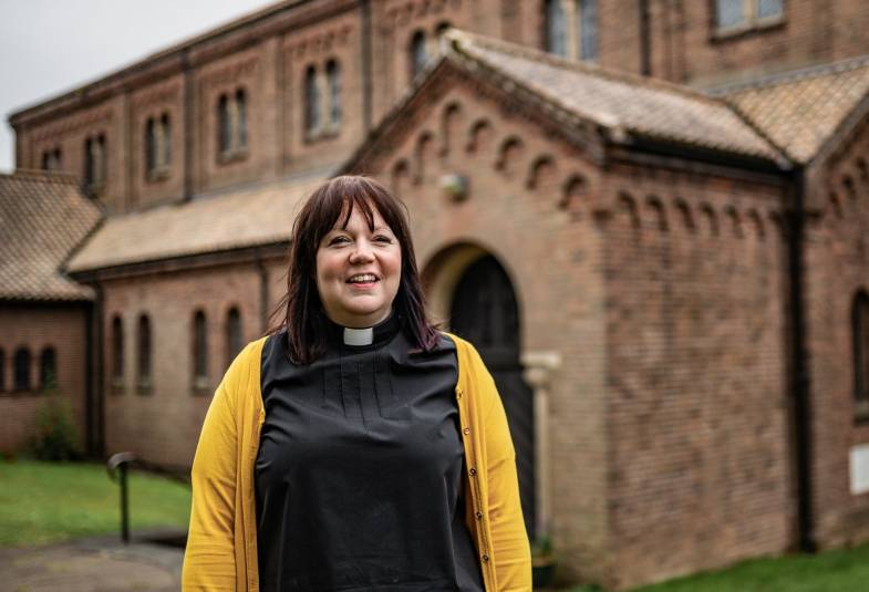 Vicar wearing a yellow cardigan and standing outside her church