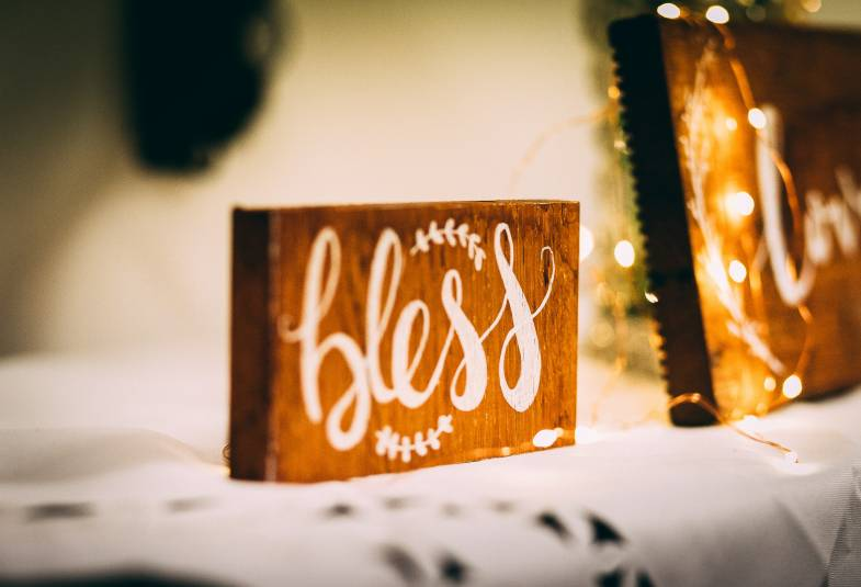 A wooden block with the word 'bless' written on it.
