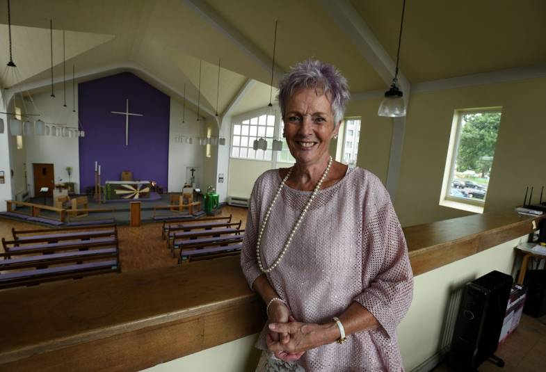 Woman with short purple hair in estate church with purple wall