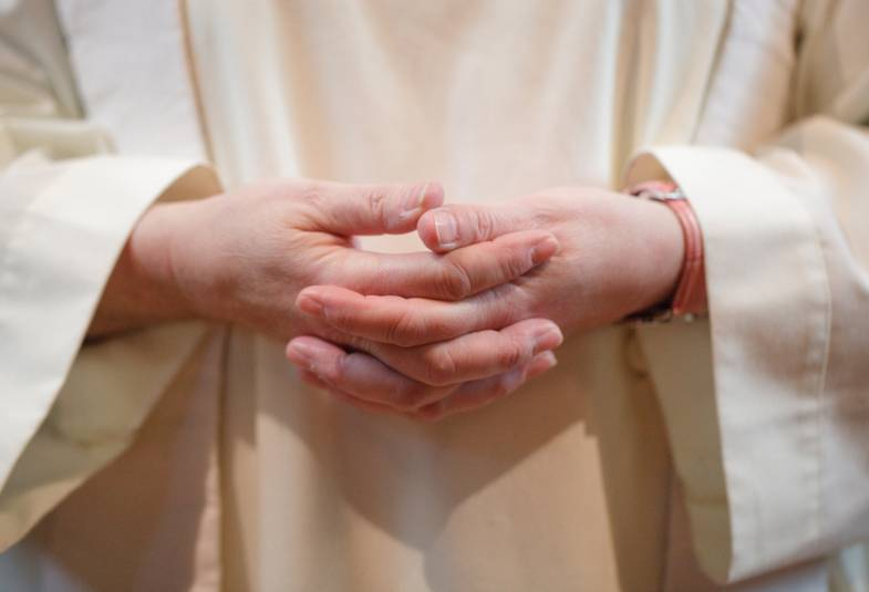 Close up of vicar's clasped hands